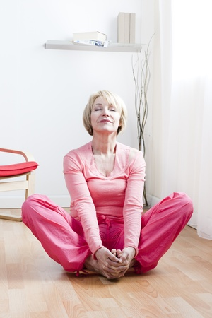 Mature Woman doing yoga exercises photo