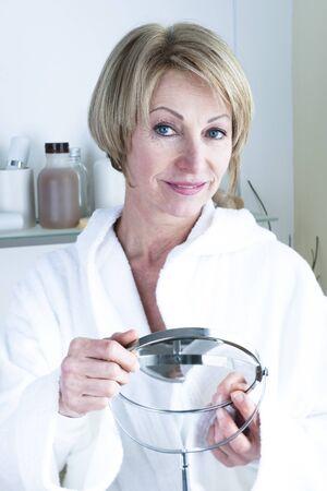 only mature women: Beautiful mature woman holding mirror Stock Photo