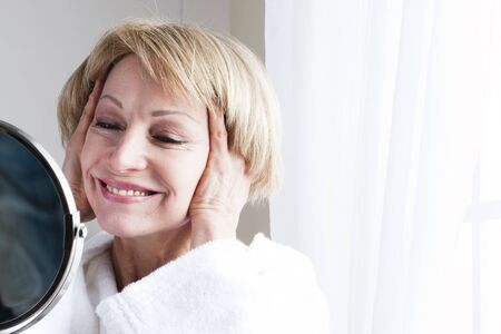 Mature woman looking at herself in the mirror Stock Photo - 8943492