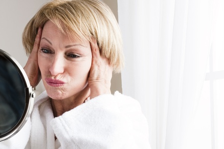 Mature woman looking at herself in the mirror photo