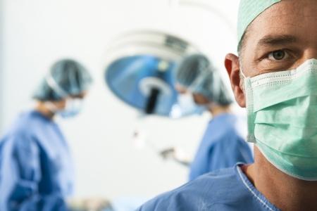 Portret van een mannelijke chirurg op het werk, mensen op tha achtergrond