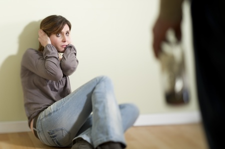 Woman scared of a man holding a bottle; Concept: abuse/domestic violence due to alcoholism photo