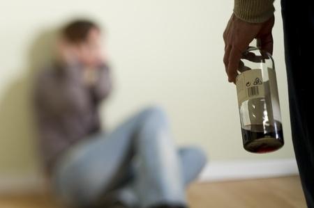 maltrato: Mujer miedo de un hombre sosteniendo una botella; Concepto: violencia dom�stica y abuso debido al alcoholismo