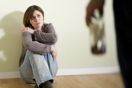 Woman scared of a man holding a bottle; Concept: abuse/domestic violence due to alcoholism Stock Photo - 9051863