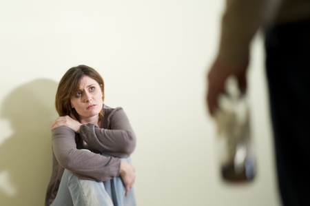 Woman scared of a man holding a bottle; Concept: abuse/domestic violence due to alcoholism Stock Photo - 9051859