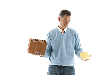 Man Holding brick and a gold bar; Concepts: investing on houes or fincancial investment photo