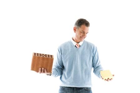 lingote de oro: Hombre con ladrillos y una barra de oro; Conceptos: invertir en la inversi�n de houes o fincancial