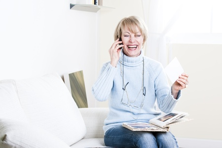 Senior woman looking at photo album and speaking on the phone photo