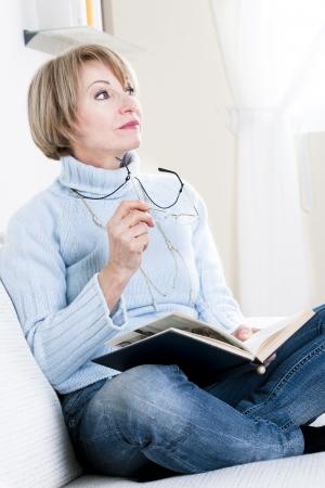 mujer leyendo libro: La lectura de la mujer mayor Foto de archivo