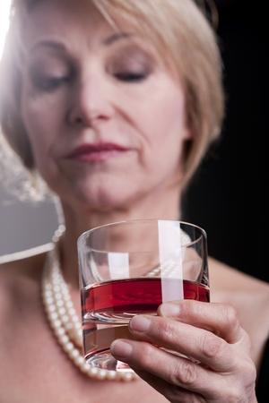 mujer pensativa: Pensativo mujer con beber, fondo negro