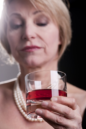 pensive woman: Pensive Woman With Drink, black background