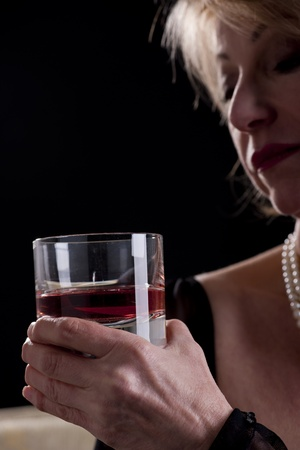 Pensive Woman With Drink, black background photo