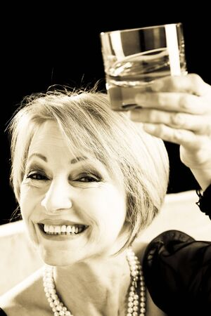 Happy Mature Woman With Drink, sepia toned image photo