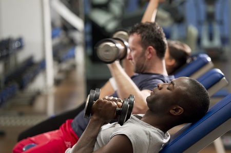 People working out with weights at health club photo