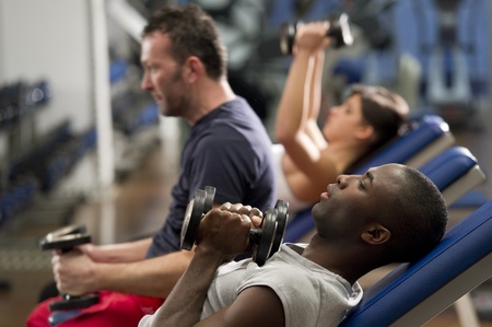 health club: People working out with weights at health club Stock Photo