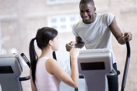 Two young people speaking while exercising at gym photo