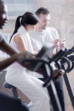 'personal beauty': Three popele biking at health club, focus on girl and perosnal trainer Stock Photo