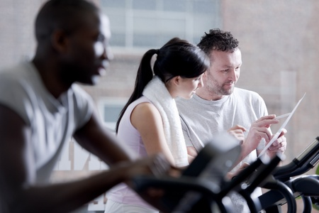 Three popele biking at health club, focus on girl and perosnal trainer photo