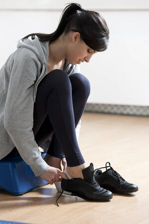 health club: Athlete at health club, tying shoes. Stock Photo