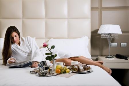 Desayuno de haber relajado de mujer en la cama, casa o habitación de hotel