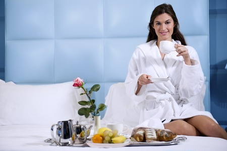 Relaxed Woman Having Breakfast in Bed, home or hotel room photo