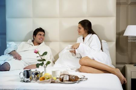 desayuno romantico: Par relajado en la cama de la habitaci�n de hotel Foto de archivo