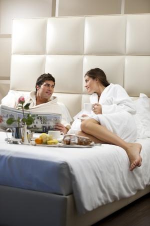 luna de miel: Par relajado en la cama de la habitaci�n de hotel Foto de archivo
