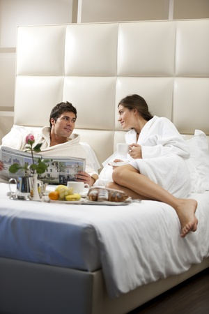 Relaxed Couple in Bed, hotel room Stock Photo - 9260322