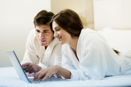 bathrobe: Relaxed couple working in bed