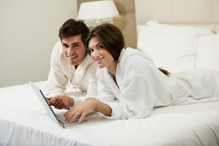 Relaxed couple working in bed Stock Photo - 9260259