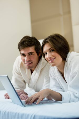 Relaxed couple working in bed Stock Photo - 9260317