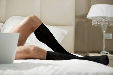 Close-up of a male legs on hotel bed Stock Photo - 13954151