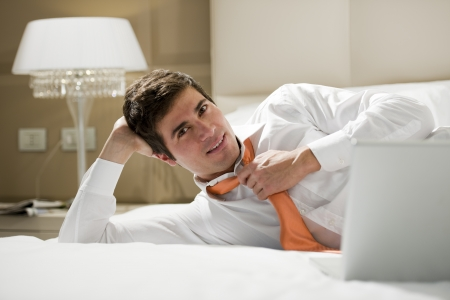 Businessman working on hotel bed
