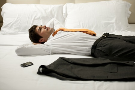 tired businessman: Tired Businessman resting in hotel room Stock Photo