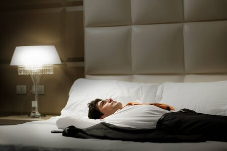 bed room: Tired Businessman resting in hotel room Stock Photo