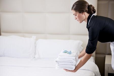 Maid machen Bed in Hotelzimmer Standard-Bild