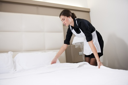 hotel service: Maid making bed in hotel room Stock Photo
