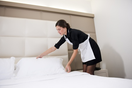 hotel worker: Maid making bed in hotel room Stock Photo