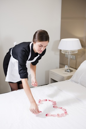 hotel suite: Maid preparing heart with petals on honymooners bed Stock Photo