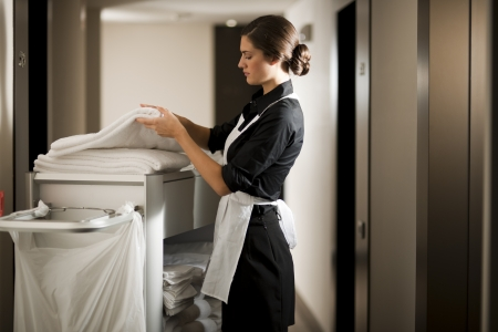 hotel worker: Maid with housekeeping cart Stock Photo