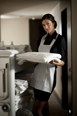 Maid with housekeeping cart photo