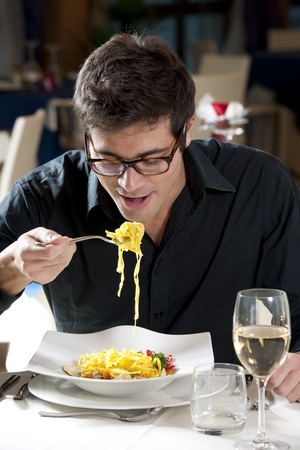 Man eating spaghetti with fish and vegetables