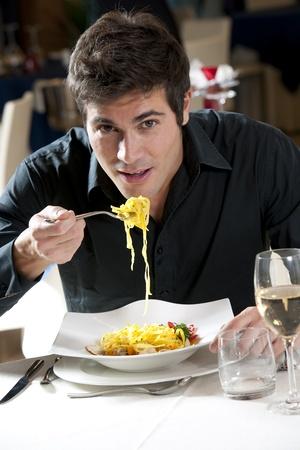 pareja comiendo: Hombre comer espaguetis con pescado y verduras Foto de archivo
