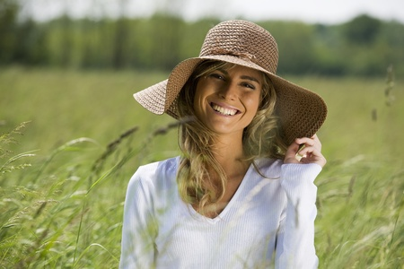 Beautiful woman in field with straw hat photo