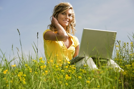 Beautiful woman sitting on the grass with her laptop Stock Photo - 9639666