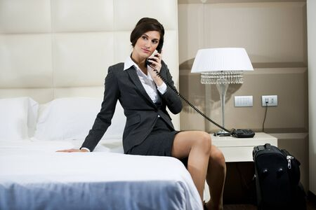 business traveler: Businesswoman on the phone in hotel room Stock Photo