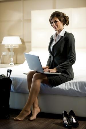 descalza: Joven empresaria en port�til en su habitaci�n de hotel