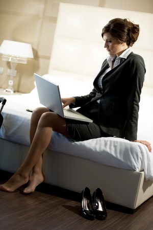 25 30 years women: Young businesswoman on laptop in her hotel room