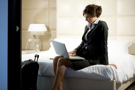 business traveler: Young businesswoman on laptop in her hotel room