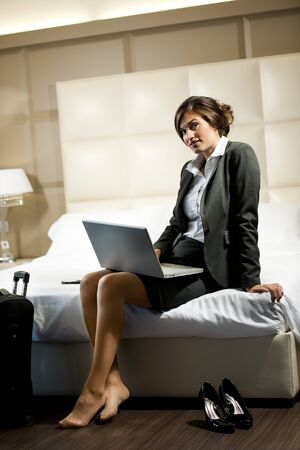 Young businesswoman on laptop in her hotel room photo